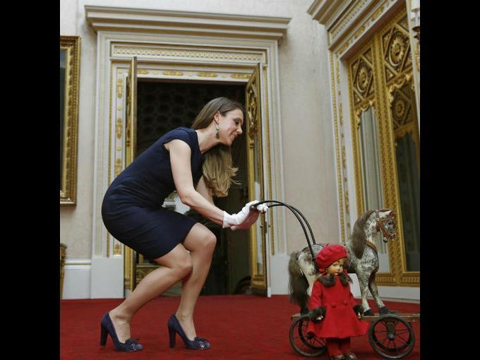 """4.La curadora de la exposición, Anna Reynolds posando con un caballo de juguete y una muñeca llamada """"Pamela"""" perteneciente a la Reina Isabel II"""