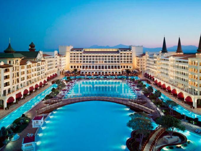 4-Hotel Mardan Palace en Turquía. Una alberca en medio de una construcción que  cuenta con miles de metros cuadrados y una gran vista de la ciudad.